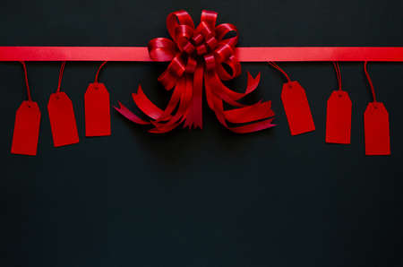 Red ribbon with bow and price tags on black background. Black friday concept. 写真素材