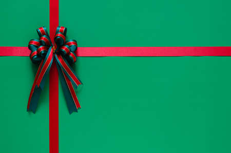 Christmas ribbon with bow on green background. Chrismas and New year concept. 스톡 콘텐츠