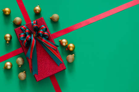 Red gift box with bow ribbon and Christmas baubles ornaments on green background. Christmas and New year concept.
