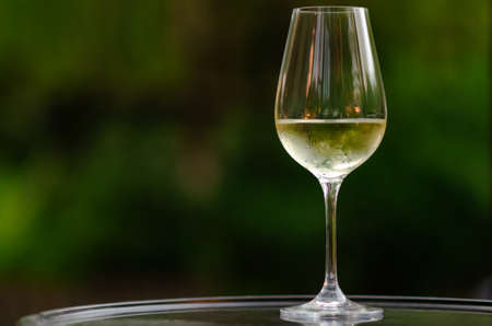 A glass of white wine on table with green background from garden.