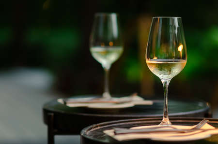 Two glasses of white wine on table with green background from garden.