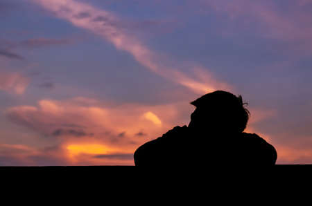Silhouette of asian man stay alone with dusk sky background. Depression and mental health concept.