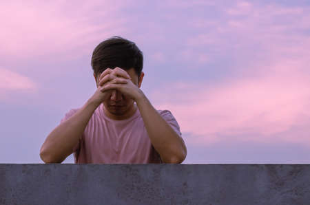 Asian miserable depressed man stay alone with sky background. Depression and mental health concept.