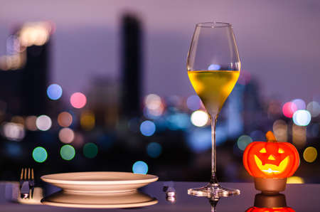 A glass of white wine with white plate, knife, fork and jack-o-lantern candle on city bokeh light background. Halloween dining concept.