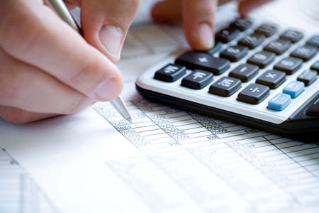 Financial data analyzing. Counting on calculator. Hand with pen on calculator. Stock Photo