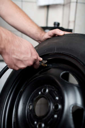 Mechanic deflating vehicle tyre closeup Stock Photo