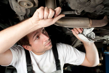 Auto mechanic working under the car photo