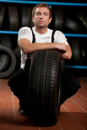 Mechanic crouching with tyre in tyre service