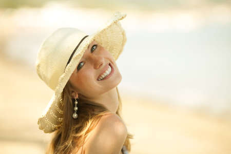 Beautiful young woman with the hat smiling on the beach. Perfect smile