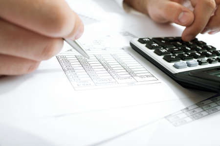 Financial data analyzing. Counting business data on the table closeup photo