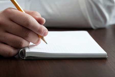 businessman writing a note with pencil