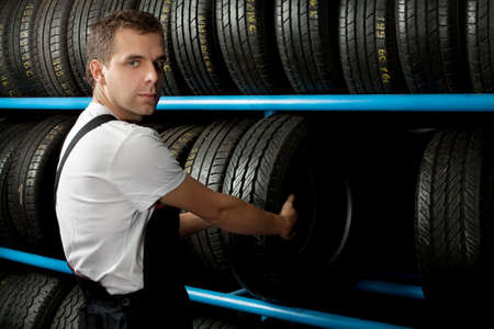 Young Mechanic holding a car tire in car service