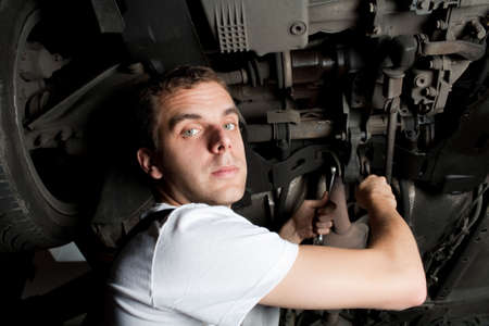 Young Mechanic working below car with wrench