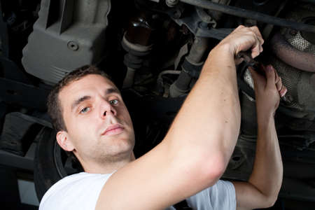 Young Mechanic working below car with wrench Stock Photo - 5625891