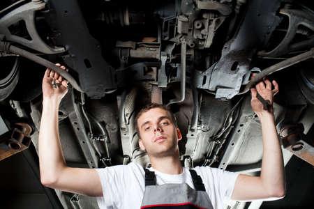 Young Mechanic working below car in uniform