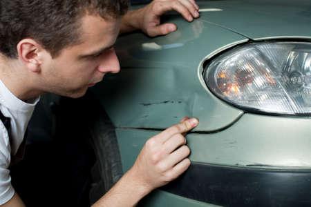 Close-up der beschädigten Auto von Mechaniker inspiziert