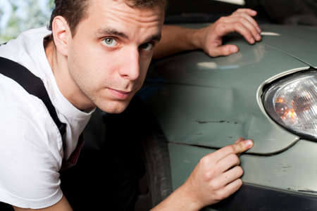 Close-up of damaged car  inspected by mechanic