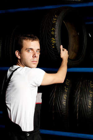 Young mechanic reaching tire in car service Stock Photo - 5625786