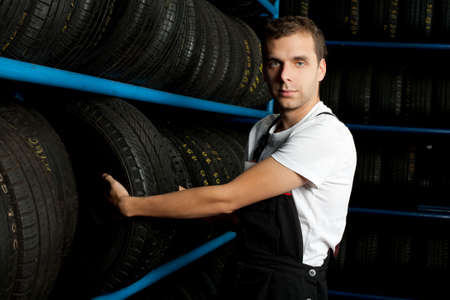 Young mechanic choosing tire in tire store Stock Photo - 5625880