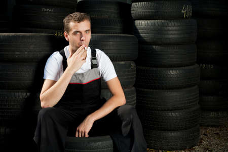 Young mechanic sitting on tire and smoking Stock Photo - 5625890