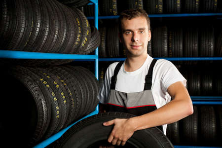 Young mechanic carrying tire in car service Stock Photo - 5625893