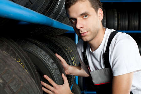 Young mechanic choosing tire in car service Stock Photo - 5625883
