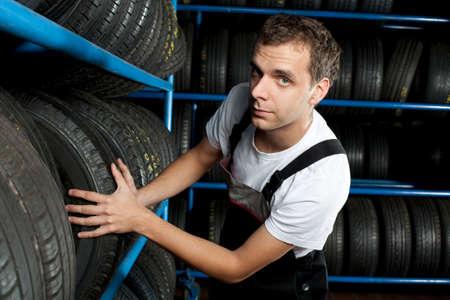 Young mechanic choosing tire in car service Stock Photo