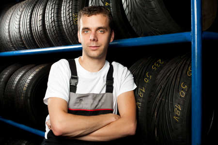 Young mechanic standing next to tire shelves in tire store photo