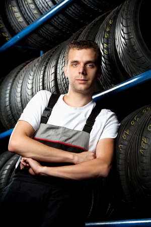 Young mechanic standing next to tire shelves photo