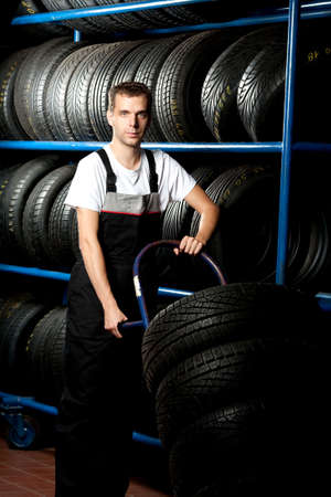 Young mechanic carrying tire in car service Stock Photo