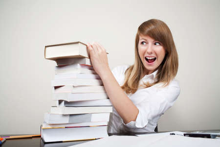 Confused student sitting at table with stack of books Stock Photo
