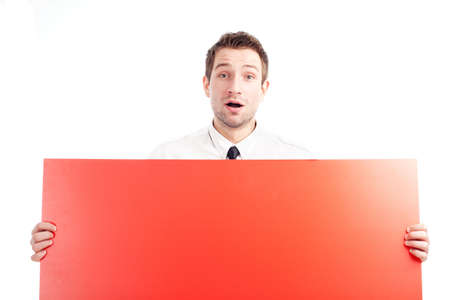 Portrait of young businessman who is holding blank red sign. He is surprised. Isolated on white. You can add your idea on the sign. Stock Photo