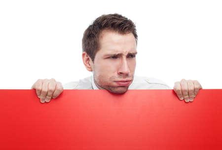 disdain: Retrato de hombre joven que se mantiene en blanco signo rojo y mostrando su desprecio. Aislados en blanco. Puede agregar su idea en el signo. Foto de archivo