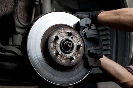 Primer plano de mecánico de reparación de automóviles pastillas de freno