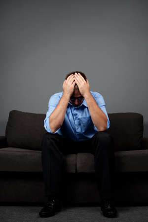 Depressed man sitting on sofa with hands on head photo