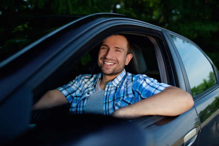 buying a car: Handsome man smiling in his own car