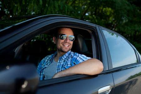 Handsome Mann lächelnd in seinem eigenen Auto