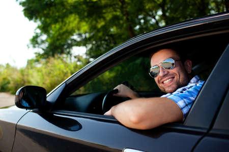 Schöner Mann lächelnd in seinem eigenen Auto