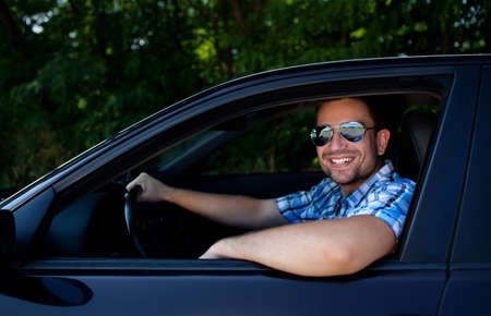 Handsome man smiling in his own car photo