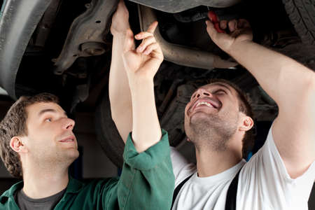 Two mechanics repairing car in garage under the car. photo
