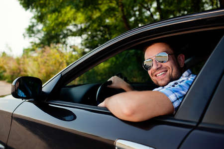 Portrait of young handsome man smiling in his own car Foto de archivo