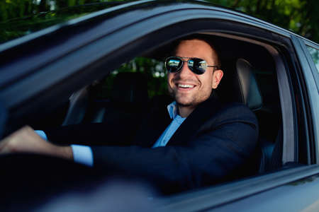 businessman in car smiling Foto de archivo