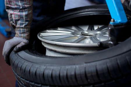 メカニックが車のタイヤのクローズ アップを変更します。