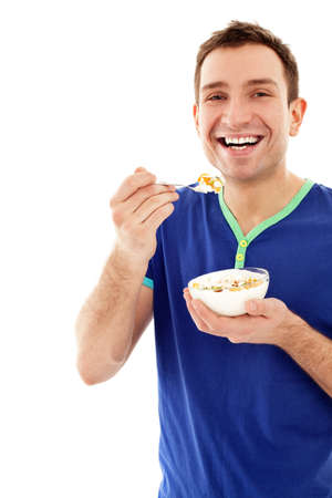 Young smiling man eating musli on diet isolated on white background