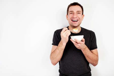 yogurt: Joven sonriente hombre comiendo Musli en la dieta aislada en el fondo blanco