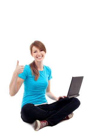 Female student sitting with laptop thumbs up. Isolated on white background Standard-Bild