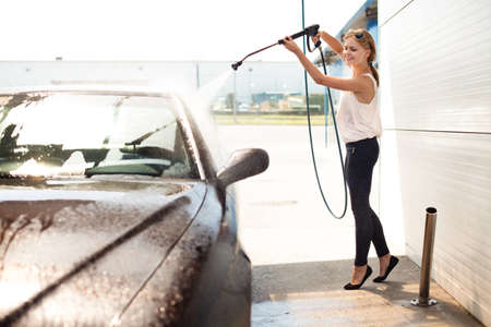 若い女性は、笑顔の車を洗います。