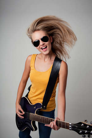 Female rockstar playing guitar. Isolated.