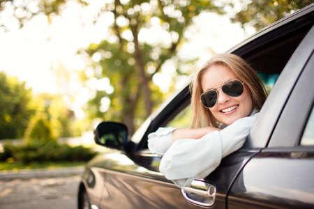 그녀의 새 차에 젊은 여자는 웃고.