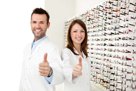 Two happy opticians, optometrists showing thumbs up in optical shop Foto de archivo